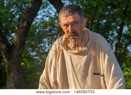 Portrait of tired bee-keeper wearing dirty linen shirt at work place