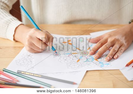 Hands of woman drawing patter on paper