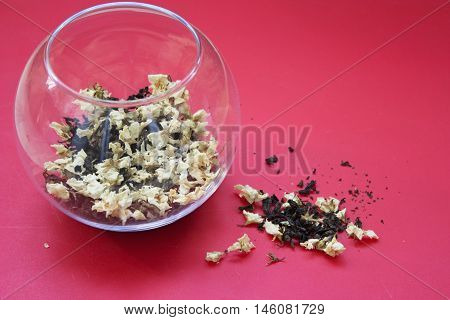 Loose tea with jasmine flowers in a glass container on a red background