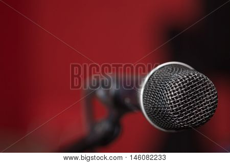 Closeup black vocal microphone mounted on mic stand, blurry red dark bcakground.