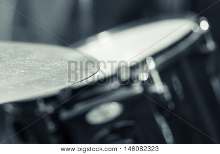 Closeup cymbal with drumkit partly visible blurry background, studio equipment concept.