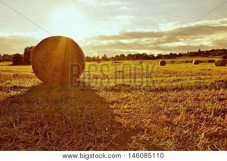 Beautiful countryside landscape. Hay bales in harvested fields.