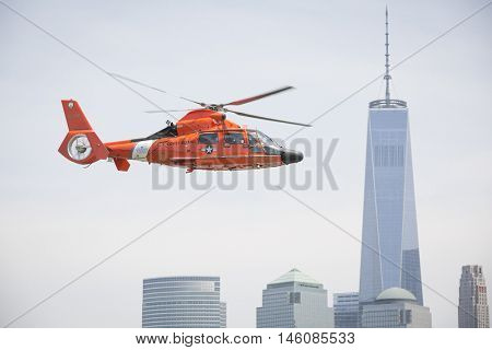 JERSEY CITY NJ MAY 29 2016: The orange U.S. Coast Guard MH-65 Dolphin helicopter passes the Freedom Tower in New York after a Search and Rescue demonstration at Liberty State Park for Fleet Week 2016.