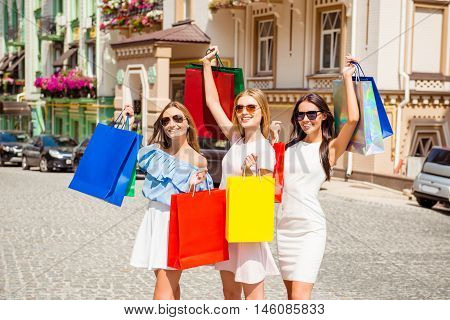 Portrait Of Three Happy Women Showing Their Purchases