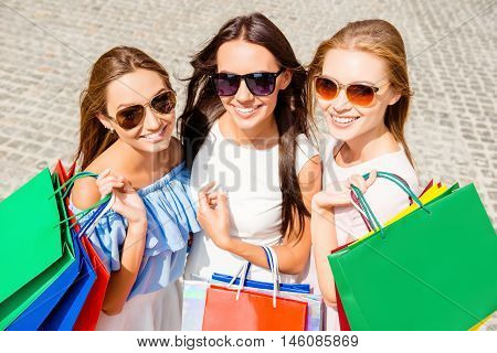 Portrait Of Three Smiling Beautiful Women In Glasses After Shopping