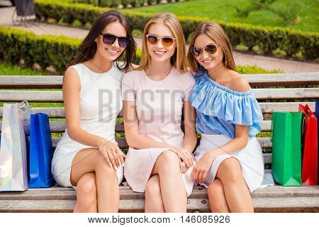 Three Beautiful Girls In Spectacles Sitting On Bench After Shopping