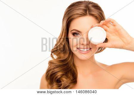 Smiling Pretty Woman Holding Jar Of Cream Near Her Eye