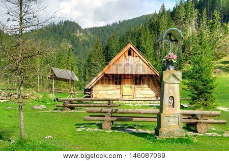 Wooden hut and shrine in beautiful mountain valley in Western Tatra Poland.