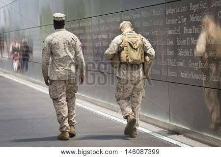 JERSEY CITY NJ MAY 29 2016: US Marine Corps personnel walk through the middle of Empty Sky, the New Jersey September 11th Memorial located in Liberty State Park, during Fleet Week 2016.