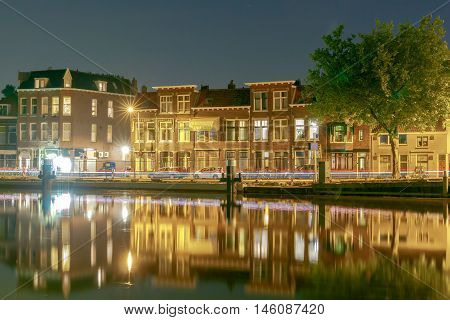 City quay with traditional Dutch houses at night. Delft. Netherlands.
