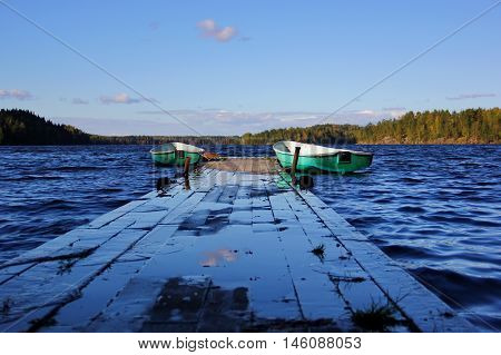 near a wooden dock, pier, tethered to two old boat light green at number five and two, deep blue lake, blue sky with clouds, a forest on the horizon