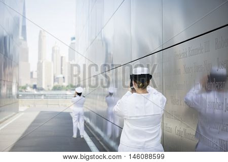 JERSEY CITY NJ MAY 29 2016: US Navy personnel take pictures of the NYC skyline from within Empty Sky, the New Jersey September 11th Memorial located in Liberty State Park during Fleet Week 2016.