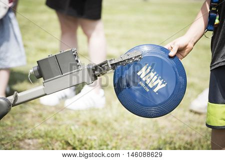 JERSEY CITY NJ MAY 29 2016:A small unmanned ground vehicle the US Navy uses to locate and dispose of explosive devices grabs a frisbee during a demonstration in Liberty State Park for Fleet Week 2016.