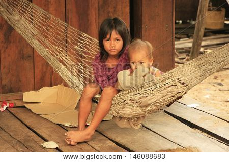 KOH RONG SAMLON, CAMBODIA - DECEMBER 13: Unidentified kids sit in a hammock on December 13, 2011 on Koh Rong Samlon island, Cambodia. Koh Rong Samlon has local village and a resort for tourists