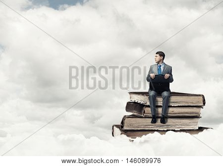 Young businessman sitting on pile of books
