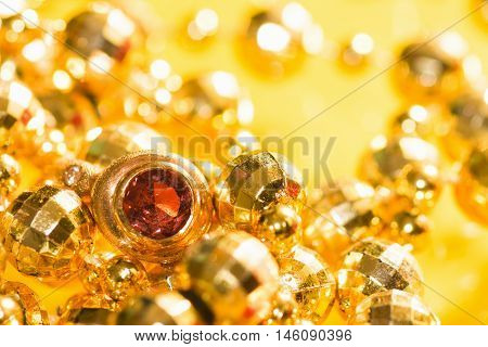 Golden jewelry and golden ring with gem are on yellow background.