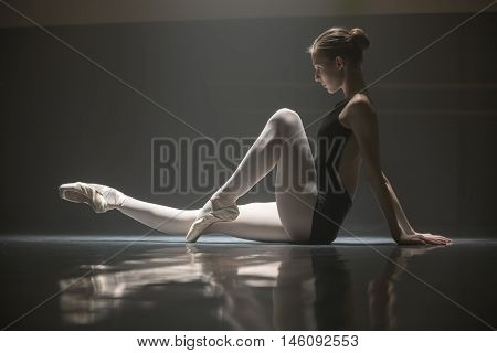 Pretty ballerina sitting on the floor in the dance hall. She leans her hands on the floor from the back while pulling one leg forward and the other bent at the knee. She is reflected on the floor surface. Light falls down from above. Low key photo.