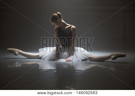 Beautiful ballerina in white tutu sitting on the splits in the dance hall. She puts her hands on the floor in front of her. She is reflected on the floor surface. Light falls down on her from above. Shoot in a low key.