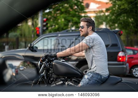 Smiling man on the black motorcycle stands in the traffic before the red traffic light. He wears blue ripped jeans, a gray T-shirt, black moto gloves and sunglasses. He has watches on the left hand. Photographed from the side. Outdoors. Horizontal.