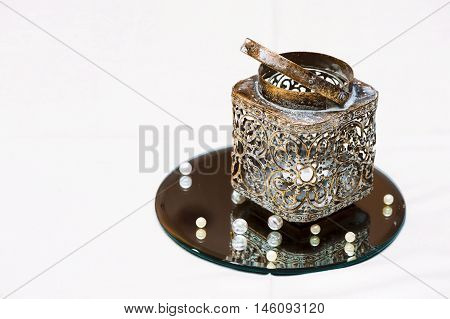A Golden candlestick with a candle on a mirrored stand and beads. Decoration of wedding table