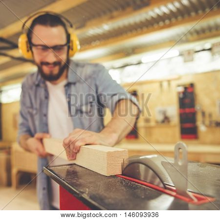 Handsome carpenter in protective glasses and headphones is smiling while working with wood and a circular saw table in the workshop