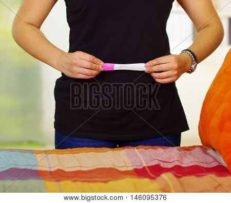 Woman wearing black dress standing up holding pregnancy home test in front, touching her own stomach, bookshelves and window garden background.