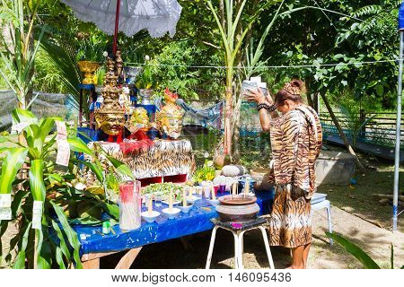 CHIANG RAI THAILAND - SEPTEMBER 1 : unidentified hermit in tiger-skin suit ritualising in front of altar tables in ancient Thai traditional style on September 1 2016 in Chiang rai Thailand.