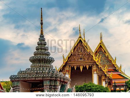 View of colorful rooftops of Temple of the Emerald Buddha or Wat Phra Kaew with cloudy sky Bangkok Thailand