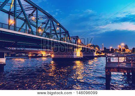 Phra Pokklao Bridge closeup over Chao Phraya River at night with lights and reflections Bangkok Thailand. Soft focus.