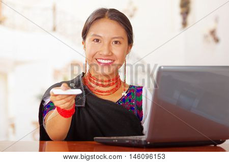 Young brunette wearing traditional native clothes working as hotel receptionist with friendly smile handing over key to client across desk, customers point of view.