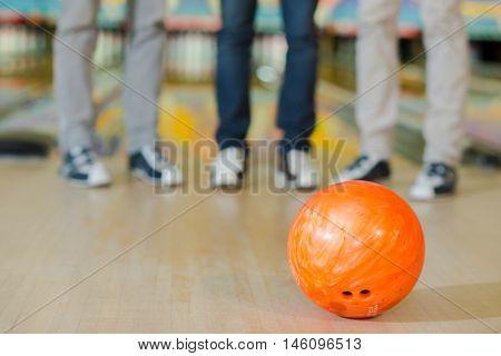 Legs of three men behind a bowling ball