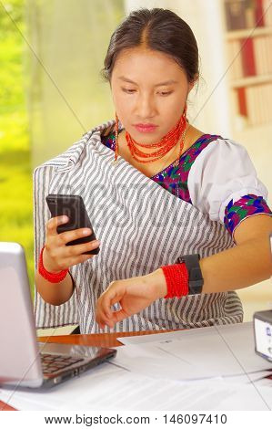 Young pretty girl wearing traditional andean clothing and glasses, sitting working by office desk with laptop computer, holding mobile phone looking at wrist watch, ring binders stacked.