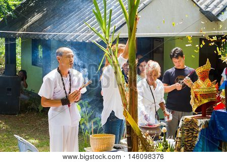 CHIANG RAI THAILAND - SEPTEMBER 1 : unidentified hermit in tiger-skin cloth and a woman ritualising in front of altar table on September 1 2016 in Chiang rai Thailand.
