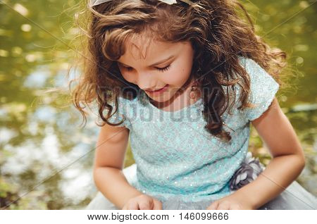 Cute little girl wearing beautiful blue dress with matching head band, posing for camera, outdoors lake background.