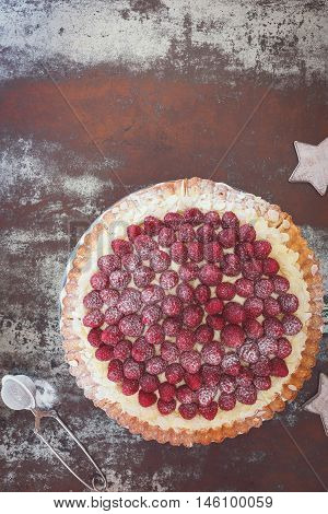 Delicious raspberry tart with with flaked almonds and fresh raspberries for Christmas. Top view, vintage toned