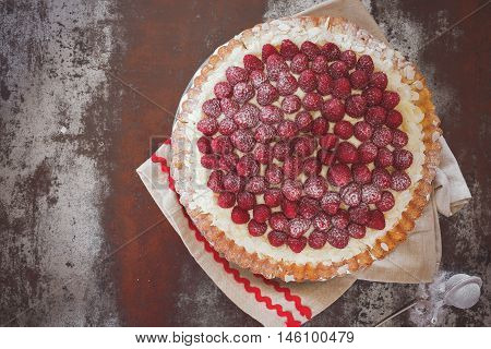 Raspberry tart with flaked almonds. Top view, vintage toned image, blank space