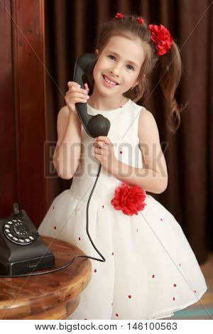 Shy little girl standing beside the round oak table. Girl holding the ear up the old phone