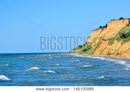 Wild Beach On A Background Of Blue Sea. Soil Erosion, Destruction Of Coastal Line On The Edge Of The