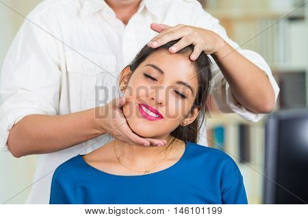 Attractive brunette office woman wearing blue sweater sitting by desk receiving head massage, stress relief concept.