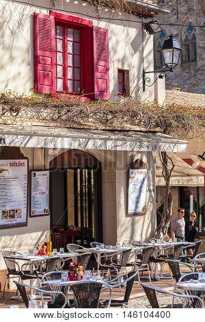 Carcassonne, France - April 1, 2011: Tourist Couple Walking Near Tables Of Street Restaurant