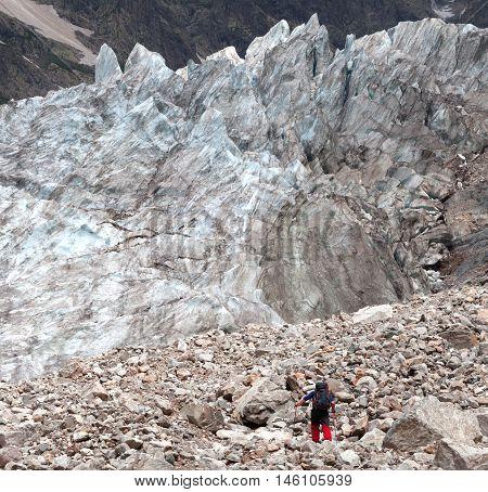 Hiker on glacier moraine. Caucasus mountains Georgia region Svanetia.