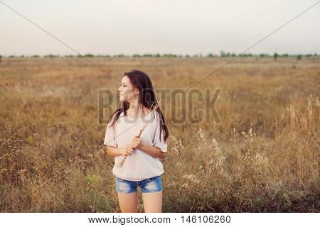 Young girl with long brown hair standing at the autumn meadow with spikelets in her hand smiling and looks left. Selective focus, warm tinted.