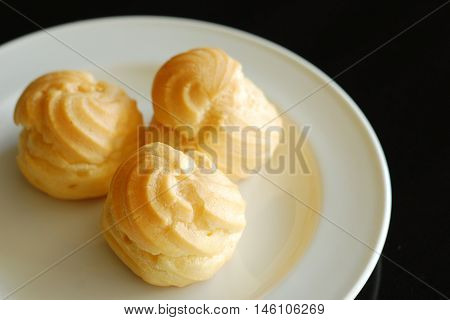 Eclairs Or Profiterole With Chocolate And Whipped Cream Preparing On Baking Sheet. Spreading Chocola
