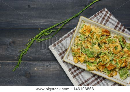 Acacia Pennata Omelette on a plate with tablecloth on wooden table