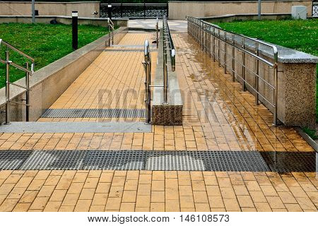 Ramp for wheelchair entrance and a staircase with metal railing