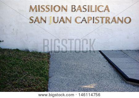 SAN JUAN CAPISTRANO, UNITED STATES - DECEMBER 25: The gold-trimmed nameplate of the Mission Basilica San Juan Capistrano on a white wall on December 25, 2015 in San Juan Capistrano.
