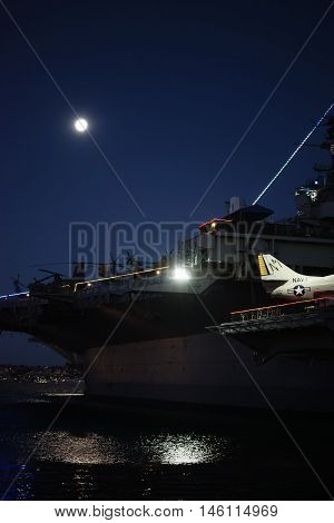 SAN DIEGO, UNITED STATES - DECEMBER 25: An old fighter plane stands on the nocturnal lit deck of the aircraft carrier and museum ship MSS Midway in Navy Pier on December 25 2015 at the Port of San Diego