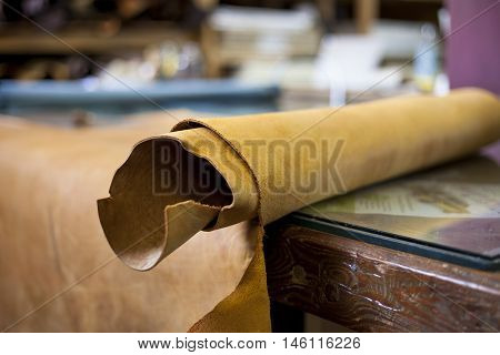 A large roll of leather at workstation before cutting.