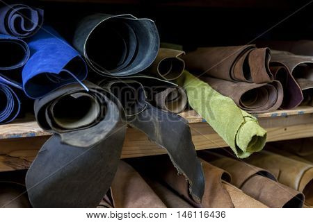 Darker colored rolls of leather sorted on a shelf.