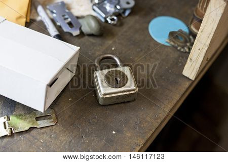 An old lock and antique hinges rest on counter for later use in bookbinding.